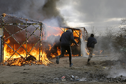 Tents are burned as the makeshift refugee camp known as the Jungle, in Calais, is dismantled. Reporters covering the French site say they have been attacked. (AP/Jerome Delay)