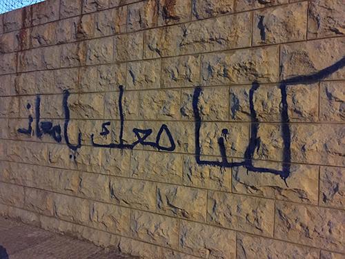 كتابة على جدار خارج مدرسة في عمان، تقول 'كلنا معك يا معاذ'، في إشارة إلى الطيار الأردني الذي أعدمه تنظيم الدولة الإسلامية في عام 2015. وقد اعتقلت السلطات صحفيين اثنين بتهمة نشر 'أخبار كاذبة'، خلال أزمة أسر الطيار. (لجنة حماية الصحفيين/جيسون ستيرن)