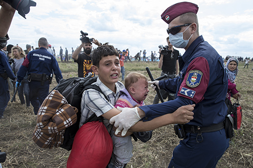 Hungarian police try to stop a young migrant with a baby in September 2015. Journalists covering the refugee story report being harassed, blocked and sometimes attacked. (Reuters/Marko Diurica)