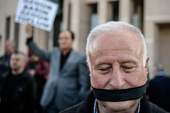 A protester covers his mouth outside the trial of two journalists from Cumhuriyet newspaper in Istanbul, April 1, 2016. (Ozan Kose/AFP)