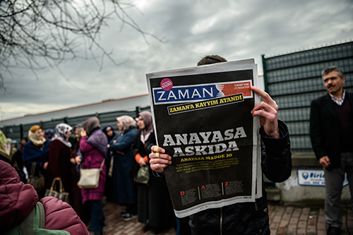 A copy of Zaman, with a headline that reads 'Suspended, the constitution,' is held up the day after the daily was taken over by court-appointed trustees. (AFP/Ozan Kose)
