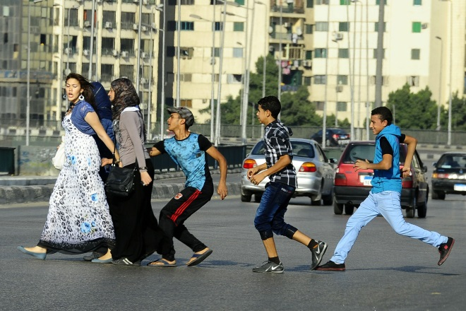 An Egyptian youth grabs a woman crossing the street with her friends in Cairo in 2012. Several women journalists were attacked in the city's Tahrir Square after the fall of Hosni Mubarak. (AP/Ahmed Abdelatif, El Shorouk Newspaper)