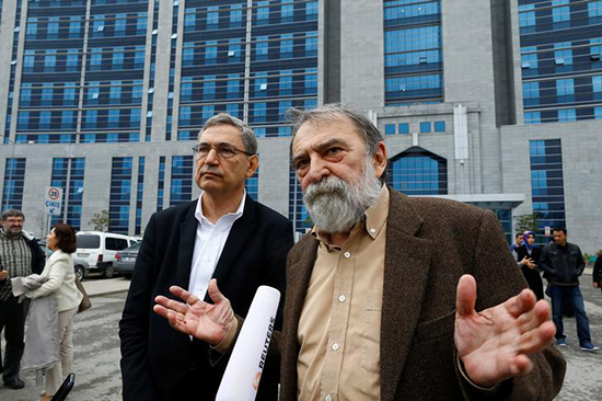 Academic and newspaper columnist Murat Belge (right) and Nobel-Prize-winning author Orhan Pamuk speak to reporters after the first session of Belge's trial in Istanbul on charges of insulting the president, May 3, 2016. (Reuters/Osman Orsal)