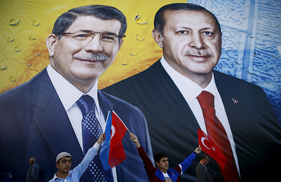 Supporters of the ruling Justice and Development Party (AKP) wave flags in front of a mural of Turkish President Recep Tayyip Erdoğan and Prime Minister Ahmet Davutoglu (left) at an election rally in Konya, Turkey, October 30, 2015. (Umit Bektas/Reuters)