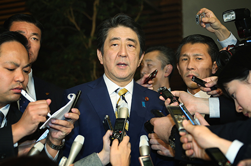 Reporters surround Japanese Prime Minister Shinzo Abe in February. Journalists say control of the media has been tightened since he came to power. (AFP/Jiji Press)