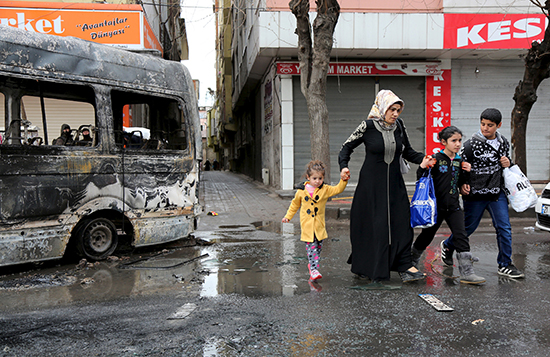 A woman and children walk past a bus damaged in fighting between ethnic Kurdish youth and security forces, in the southeastern Turkish city of Diyarbakir, March 15, 2016. Pro-Kurdish journalists have faced terrorism charges for their reporting on clashes between ethnic Kurdish youth and security forces in the region since peace talks between the Kurdistan Workers' Party (PKK) and the government unraveled in 2015. (Sertac Kayar/Reuters)