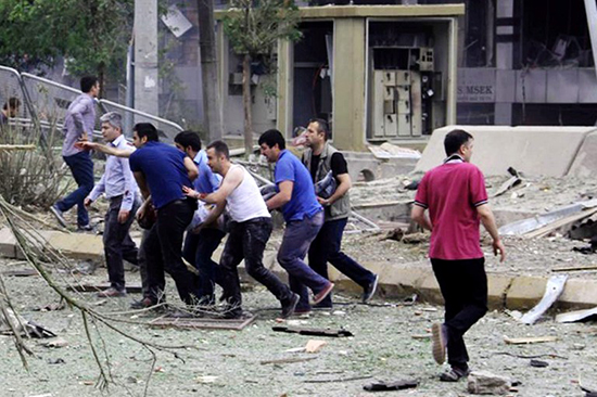 Onlookers help a man injured in a June 8, 2016, bombing in the southeastern Turkish town of Midyat that killed at least three people and injured at least 30 more. Residents attacked journalists filming the aftermath of the explosion. (AFP)