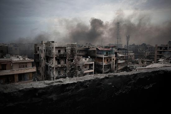 Smoke rises over Aleppo's Saif al-Dawla district in this October 2, 2012, file photo. (Manu Brabo/AP)