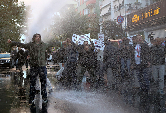 Police use water cannons to disperse protesters in front of the Istanbul headquarters of the Koza İpek media group after a court ordered it put into trusteeship, October 28, 2015. A columnist for Bugün, one of the group's former holdings, was released on June 10, 2016, after seven months' pre-trial detention. (Mehmet Ali Poyraz/Cihan News Agency/AP)