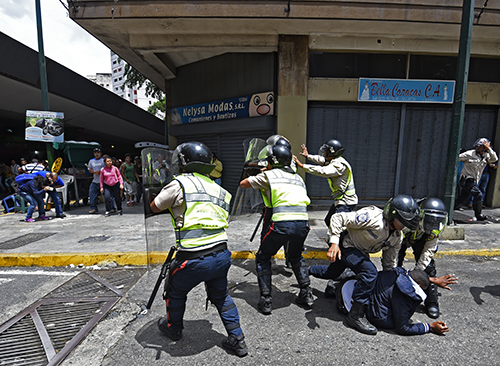 Security forces and residents clash during a protest over food shortages in Caracas on June 2. Several journalists were attacked during the protest. (AFP/Juan Barreto)