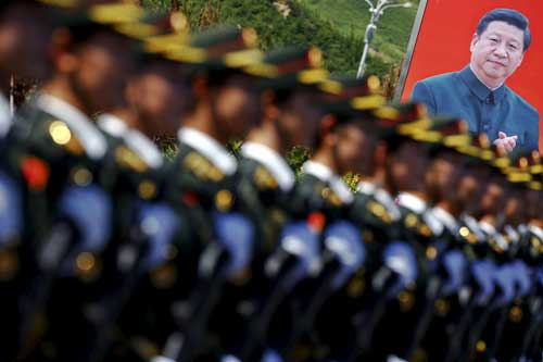 A picture of Chinese President Xi Jinping is seen behind People's Liberation Army soldiers in Beijing on August 22, 2015. (Reuters/Damir Sagolj)