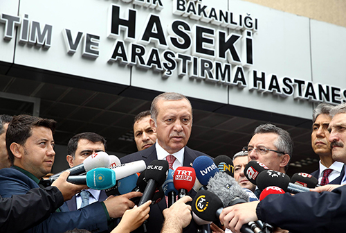 President Erdoğan talks to the press outside an Istanbul hospital in June after a police bus was attacked. At a news conference on the more recent airport attack, Turkey's leader said he was against social media. (AFP/Yasin Bulbul)