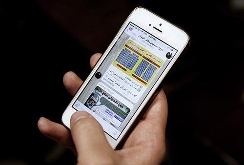 Iraniano mostra mensagens no aplicativo Telegram sobre eleições do Irã em fevereiro. Especialistas em segurança alertam que os usuários do aplicativo pode estar colocando em risco o sigilo de dados. (AP/Vahid Salemi)