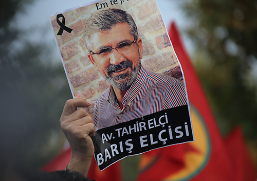 "A poster is held up of Tahir Elçi, a lawyer shot dead in Turkey last year. A reporter for DİHA was questioned this week for ""insulting the president"" after allegedly sharing a political cartoon about the lawyer's death. (AP Photo/Mahmut Bozarslan)"