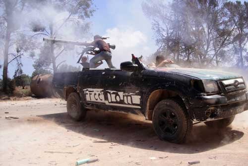 This June 20, 2011, photo by Abdelqadir Fassouk shows rebel fighters firing a rocket toward pro-Qaddafi forces on the front line in Misrata, Libya. Fassouk was killed on July 22, 2016, while covering clashes between government-allied forces and the militant group Islamic State. (AP/Abdelqadir Fassouk)