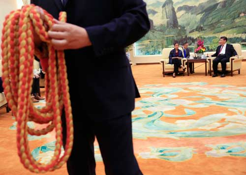 A Chinese security officer holds the media rope as U.S. National Security Adviser Susan Rice, background left, and Chinese President Xi Jinping, right, are seated for photographers at the Great Hall of the People in Beijing on July 25, 2016. Xi's increasing intolerance of negative coverage has approached a kind of lèse-majesté. (AP/How Hwee Young)