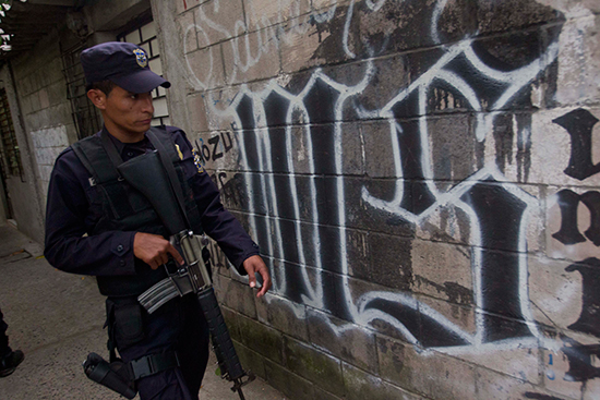 In this 2014 file photo, a policeman walks next to graffiti from the Mara Salvatrucha criminal gang. If his recent conviction on defamation charges is upheld on appeal, TV reporter Ariel Armando D'Vicente faces three years in prison and a three-year ban on practicing journalism in connection with reports alleging police took bribes from gangs involved in smuggling. (AP/Esteban Felix)
