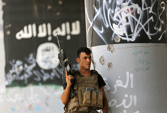 A member of Iraq's counter-terrorism forces stands guard in front of graffiti left behind by fleeing members of the Islamic State group in Fallujah, June 27, 2016. (AP/Hadi Mizban)