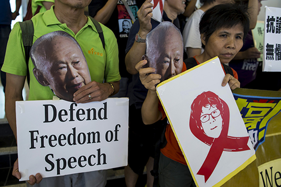 Demonstrators protesting the trial of blogger Amos Yee hold pictures of the late Lee Kuan Yew, founder of modern Singapore, on July 5, 2015. (Reuters/Tyrone Siu)