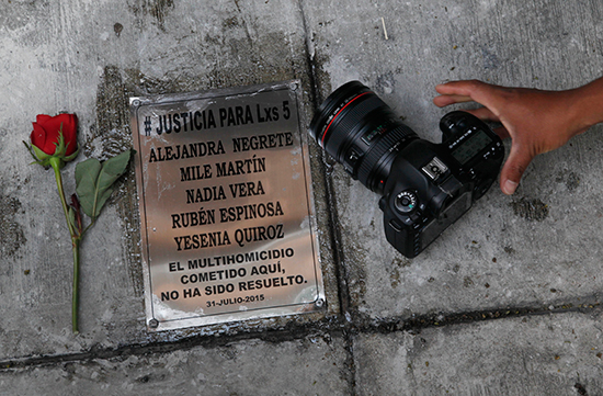 A photographer sets his camera beside a plaque commemorating photojournalist Ruben Espinosa and four women murdered with him in Mexico City in 2015 on the anniversary of their deaths, July 31, 2016. Espinosa worked with the investigative magazine Proceso and other media in the state of Veracruz at the time of his murder. (AP/Marco Ugarte)