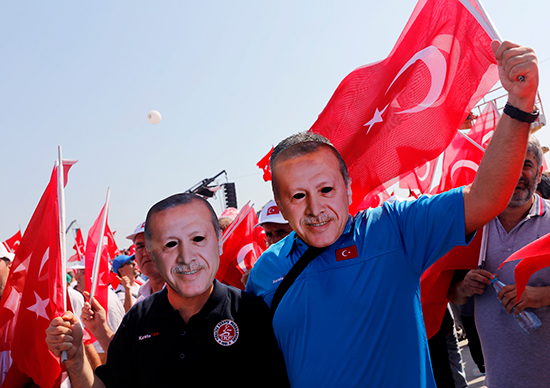 Participants in an August 7, 2016, pro-government rally in Istanbul wear masks depicting Turkish President Recep Tayyip Erdoğan (Reuters/Umit Bektas)