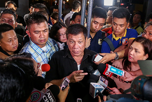 Philippine President Rodrigo Duterte, center, speaks with journalists in June. The new leader has given mixed messages on press freedom. (AFP/Manman Dejeto)