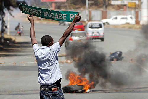 A man carries a street sign in Harare as protesters clash with police on August 26. Journalists have been beaten and detained while covering unrest in Zimbabwe. (Reuters/Philimon Bulawayo)