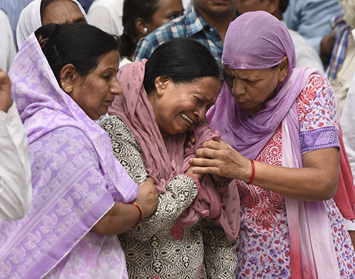 Askhay Singh's mother is comforted at the journalist's cremation in Delhi. Several dignitaries attended the service. (Getty Images/Hindustan Times)