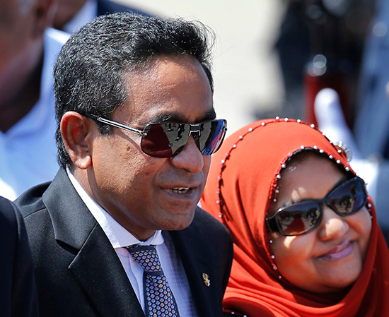 Maldivian President Yameen Abdul Gayoom (left) arrives in Sri Lanka in this January 12, 2014, file photo. Police raided the office of the Maldives Independent on September 7 after its editor was interviewed in an Al-Jazeera documentary alleging corruption and abuse of power under Gayoom's government, allegations his government has denied.