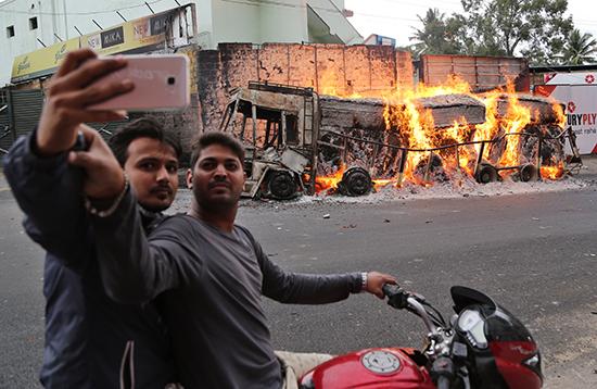 Men in Bangalore, India, take a selfie in front of a truck protesters had set ablaze, September 12, 2016. (AP/Raijaz Rahi)