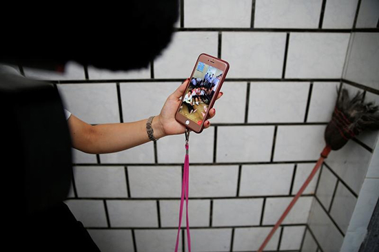 A woman shows footage on her mobile phone she says shows residents of Wukan, in China's Guangdong province, detained by police, September 14, 2016. (Reuters/Damir Salgoj)
