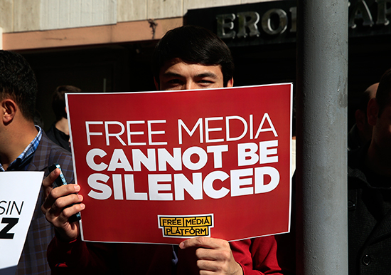 "In this October 28, 2015, file photo, a demonstrator holds a sign reading ""Free media cannot be silenced"" at a protest in Istanbul. (AP/Lefteris Pitarakis)"