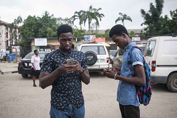 Two brothers use gaming apps on their smartphones in Lagos. Nigeria's new cybercrimes act has been used against at least five critical bloggers. (AFP/Stefan Heunis)