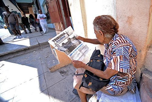 A woman reads a state-run newspaper in central Havana. The official press has been emboldened by Castro's comments that the media should be more critical. (AFP/Flippo Monteforte)