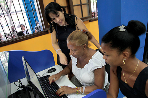 A member of Cuba's sole internet provider, ETECSA, helps customers at a Havana cyber café. The number of publically accessible Wi-Fi spots has increased, but bloggers say more are needed. (STR/AFP)