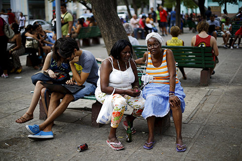 Cubans make use of a Wi-Fi access point in a square in Havana. Access to the internet costs $2 an hour. (Reuters/Ivan Alvarado)