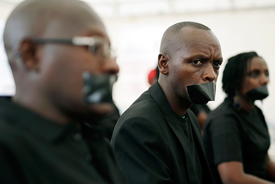 Burundian journalists mark World Press Freedom day, May 3, 2015, by taping their mouths shut to protest worsening conditions for the press in Bujumbura. (AP/Jerome Delay)
