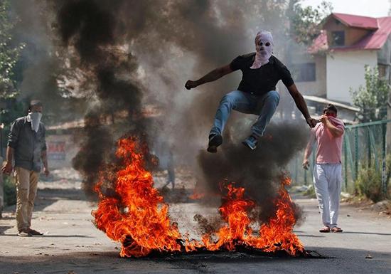 A protester jumps over burning debris in Srinagar, Jammu and Kashmir, September 12, 2016. (Reuters/Danish Ismail)