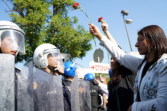 A demonstrator carrying a carnation to commemorate last year's bombing of a train station in Ankara meets a policeman in riot gear, October 10, 2016. (Reuters/Umit Bektas)
