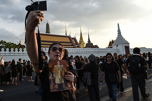 A woman takes a selfie with a picture of King Bhumibol Adulyadej after the hearse carrying his body goes by. News broadcasts have been replaced with royal footage after the king's death. (AFP/Lillian Suwanrumpha)