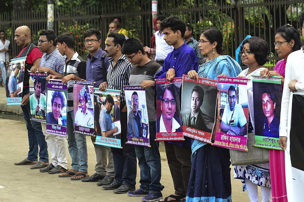 متظاهرون في دكا يحملون صوراً لكتاب ونشطاء قُتلوا على يد المتطرفين. المدونون العلمانيون هم الصحفيون الأكثر عرضة للخطر بسبب عملهم في بنغلاديش. (وكالة الأنباء الفرنسية/منير أوز زمان)