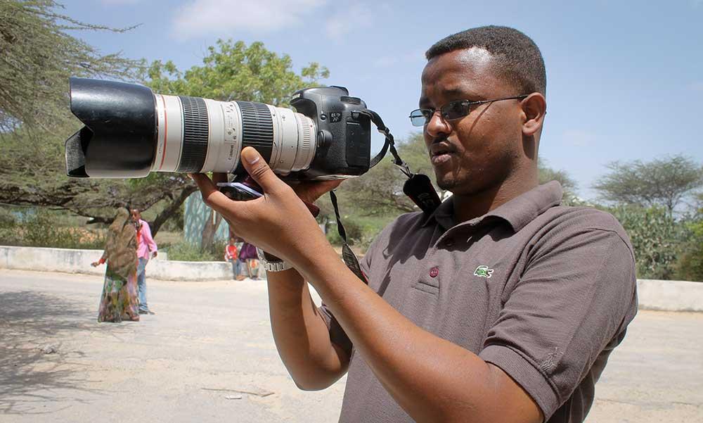 مصور قناة 'يونيفيرسال' التلفزيونية، محمد محمود، في صورة التُقطت له في كانون الثاني/يناير 2013. وتُعتبر حركة الشباب الصومالية المشتبه الرئيسي في مقتل هذا الصحفي وعديدين غيره من الصحفيين الصوماليين. (أسوشيتد برس/ فرح عبدي وراسامه)