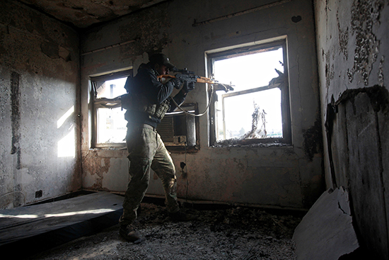 A sniper of the Iraqi rapid response team fires from the window of a hospital in eastern Mosul damaged by fighting with members of the Islamic State group, January 8, 2017. (Reuters/Alaa Al-Marjani)