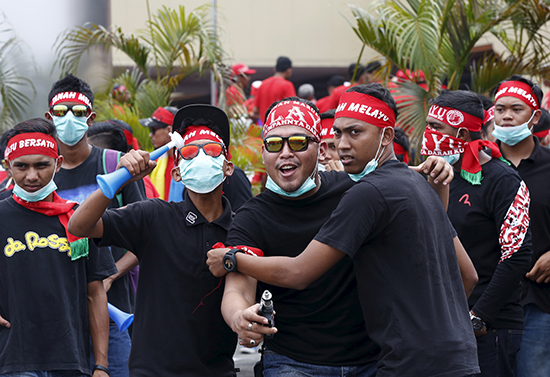 """Members of the pro-government """"red shirt"""" group, shown here in a September 16, 2015, file photo, protested outside news website Malaysiakini's office in Kuala Lumpur on November 5. The group's leader had threatened to """"tear down"""" its office two days prior. (Reuters/Olivia Harris)"""
