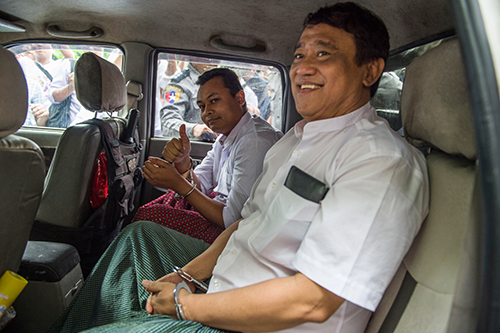 Eleven Media Group's chief executive, Than Htut Aung, right, and chief editor Wai Phyo, are handcuffed in a police vehicle on November 11, over a criminal defamation case. (Romeo Gacad/AFP)