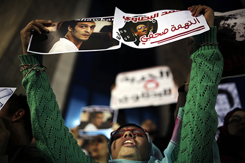 Posters calling for the release of photojournalists Mohammad al-Batawi, right, and Shawkan, are held up in Cairo. A U.N. working group says that Shawkan's detention is arbitrary. (AP/Amr Nabil)