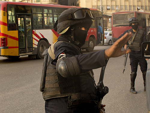 A masked policeman gestures to a photographer in Cairo ahead of planned protests on November 11. At least four journalists were detained covering areas where rallies were due to take place. (AP/Amr Nabil)