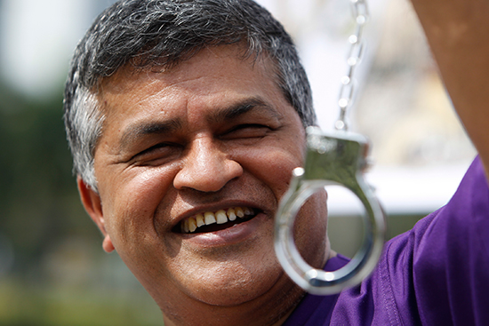 Cartoonist Zulkiflee Anwar Ulhauqe, better known as Zunar, poses in prison clothes with plastic handcuffs at a February 2, 2015, event launching a book in Petaling Jaya, Malaysia. (AP)