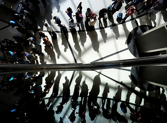 Travelers are reflected in glass as they line up for security at the international airport in Atlanta, Georgia, March 10, 2016. (AP/David Goldman)