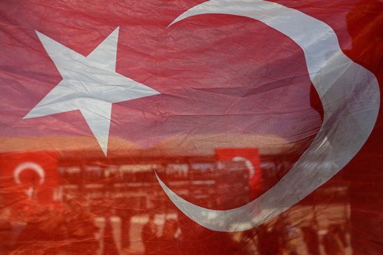 Seen through a Turkish flag, people gather outside Istanbul's Vodafone Stadium to pay respects to those killed in a bombing, December 11, 2016. Turkish authorities imposed a ban on coverage of the attack. (AP/Emrah Gurel)